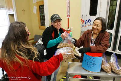 Oroville point in time coordinator Carol Zanon (right) hands bags of dog food to Melissa Hoeldt (center) and Marion Frank January 25, 2017 at the Hope Center in Oroville, California.  (Emily Bertolino -- Mercury Register)