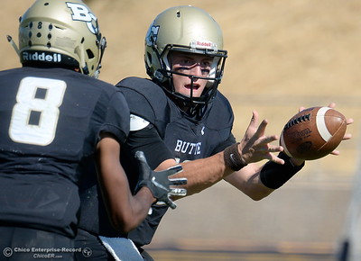 Butte's Brandt Hughes (12) gives a quick inside flip to Saivon Brown (8) during Butte vs Feather River College football at Cowan Stadium in Chico, Calif. Saturday Oct. 13, 2018. (Bill Husa -- Enterprise-Record)