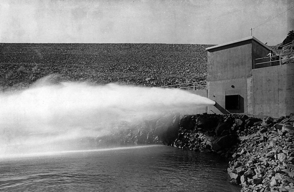 . From the Times-Call photo archive via Longmont Museum: Button Rock Dam water bursts forth from the bypass pipe below the dam into the North St. Vrain River on its way to the Longmont filter plants near Lyons. The bypass pipe is used during low water demand periods, while the square opening above it emits a much greater gush when Longmont water needs are greater. Photo from 1974. (Longmont Times-Call File/Longmont Museum)