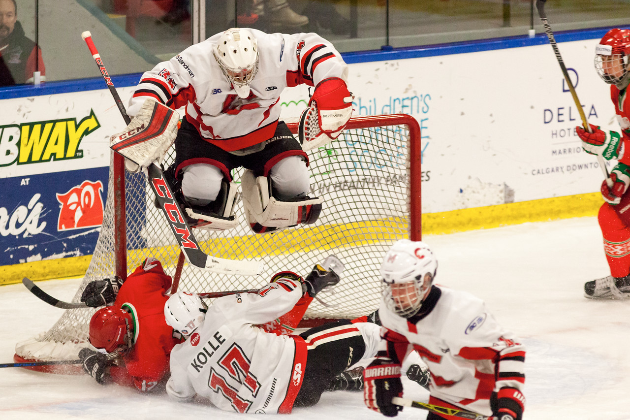 December 31, 2016 - Mac's Midget Tournament, Max Bell Centre, Calgary, Alberta - Male Division Semi-Final - Cariboo Cougars vs. Belarus National U17 - Cougars goalie #35 Zachary Wickson gets good air avoiding a collision of players at the net.