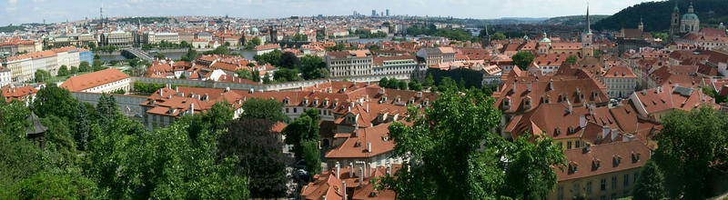 Panoramic view of Prague: Little Quarter Riverside in the foreground, the Charles Bridge and the Vltava River are visible in the center, historic Old Town Prague is in the background.