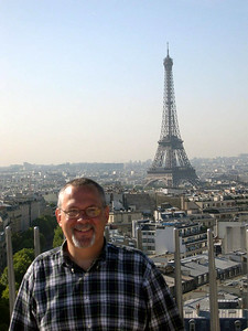 Ed on top of the Arc de Triomphe with the Eiffel Tower in the background.