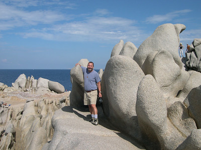Joe exploring the rocky formations of Capo Testa.
