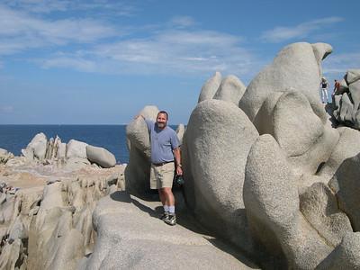 Joe exploring the rocky formations of Capo Testa.