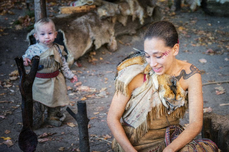 Native American Life: Wampanoag Interpreter and Child in Traditional Native American Dress Cooking Over A Fire. Plimoth Plantation, Plymouth County, Plymouth, Massachusetts
