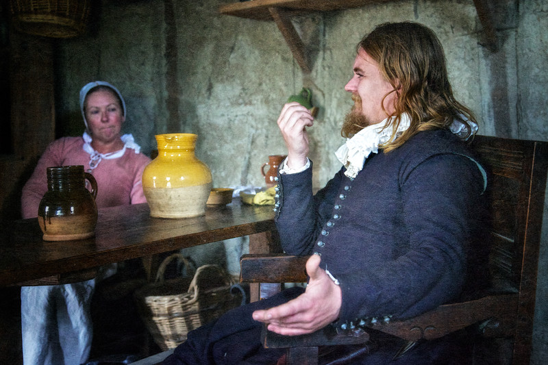 Life in Plymouth Colony: Costumed Male and Female Interpreters Sitting at Wooden Table, Candle and Plates, 1627 English Village, Plimoth Plantation, Plymouth, Massachusetts