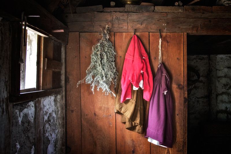 Life in Plymouth Colony: Children's Clothing, Coats and Herbs Hanging on Pegs on a Wall, 1627 English Village, Plimoth Plantation, Plymouth, Massachusetts