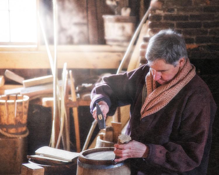 Nineteenth Century Daily Life:  Male Interpreter Working In Interior of Cooper Shop, Fixing A Barrel. Freeman Farm, c. 1840. Old Sturbridge Village, Worcester County, Massachusetts