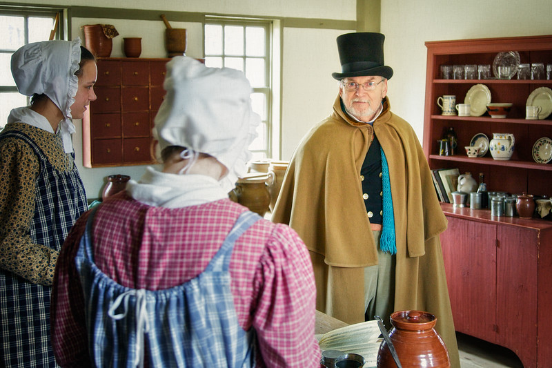 Nineteenth Century Daily Life:  Two Female Interpreters with Bonnets and Aprons and Male Interpreter in Top Hat and Cloak in Kitchen. Freeman Farm, c. 1800-1810. Old Sturbridge Village, Worcester County, Massachusetts