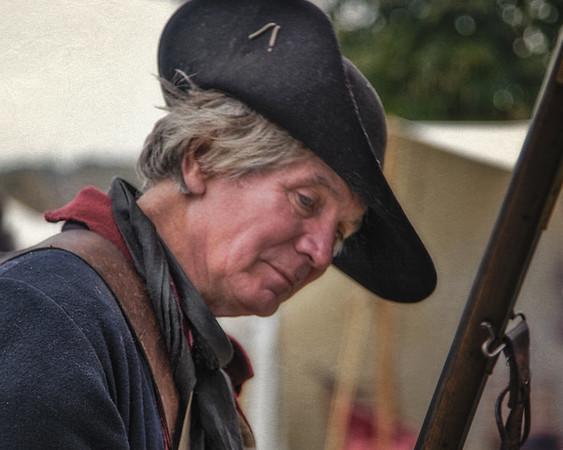 Colonial Era Reenactor Inspecting His Musket. Burning of Kingston Revolutionary War Reenactment, Kingston, Ulster County, New York