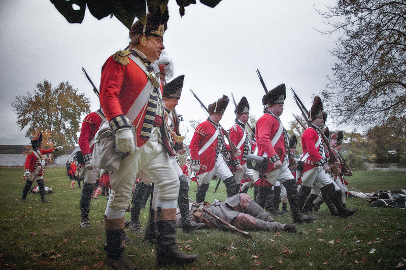 Redcoated British Advancing Through Colonial American Casualties. Burning of Kingston Revolutionary War Reenactment, Kingston, Ulster County, New York
