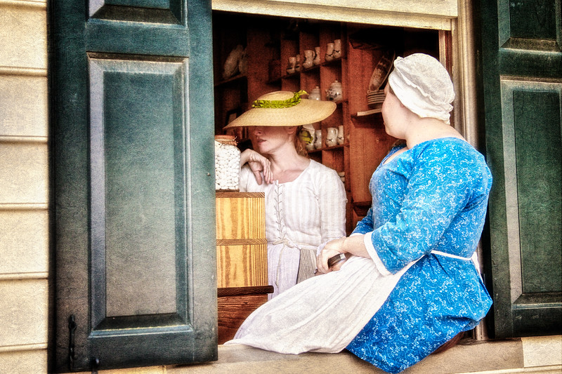 Colonial Era Daily Life: Comstumed Female Interpreter Sitting in A Shop Window. Colonial Williamsburg, WIlliamsburg, Virginia