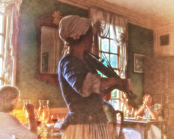 Colonial Era Daily Life. Costumed Female Fiddler at Christiana Campbell's Tavern. Colonial Williamsburg, WIlliamsburg, Virginia