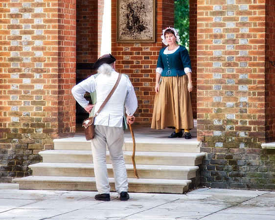 Colonial Era Daily Life. Costumed Female and Male Interpreters on the Steps of the Capital Building. Colonial Williamsburg, WIlliamsburg, Virginia