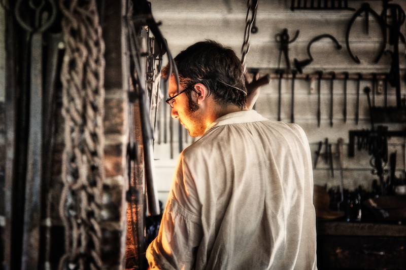 Colonial Era Daily Life. Costumed Interpreter Working in Anderson's Blacksmith Shop and Public Armoury. Colonial Williamsburg, WIlliamsburg, Virginia