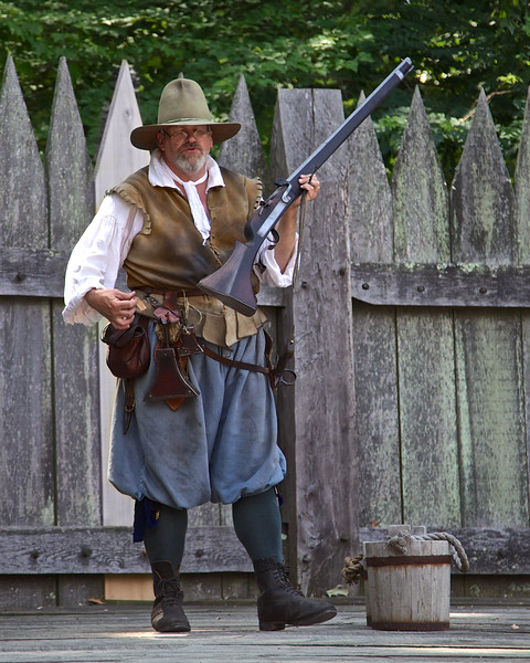 Costumed Colonial Interpreter Demonstrating Muskets