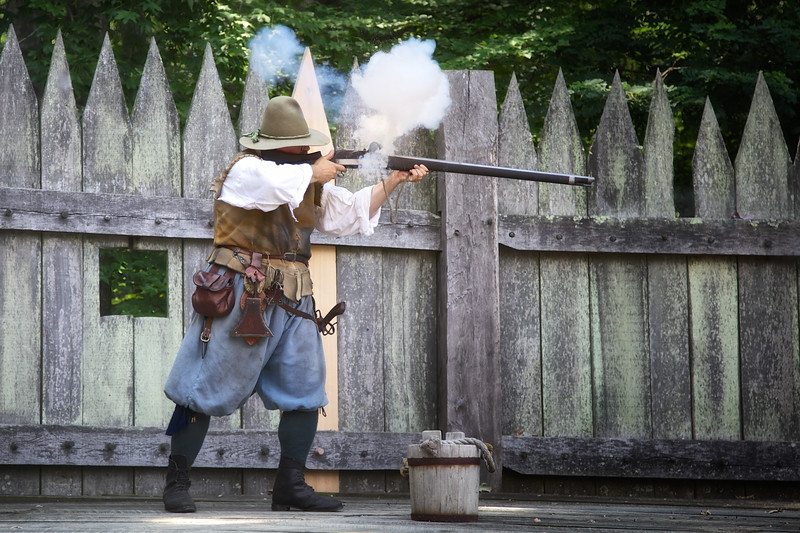 Costumed Colonial Interpreter Firing A Musket
