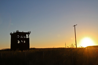 A building shell and telephone poles at sunset on Mare Island