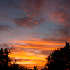 The day's last golden beams of sun paint the clouds gold and pink as night approaches.