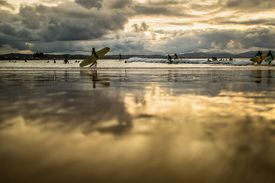 Surfers at Byron Bay beach at sunset.