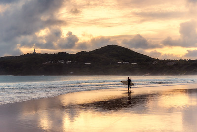 Surfer at Byron Bay at sunrise.