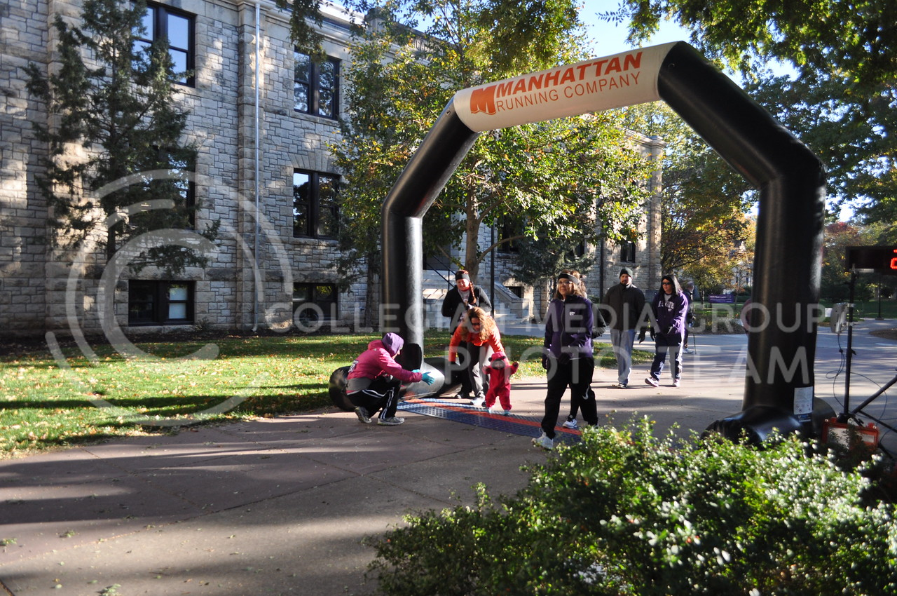 Running or walking, participants in the C. Clyde Fun Run and Midge's Mile Walk cross the finish line Oct. 28, 2017 in front of Seaton Hall.  The 5K fun run and Midge's Mile Fun Walk was held to raise money for Shepherd's Crossing, a community charity that helps residents pay bills and rent when they are in hard times.