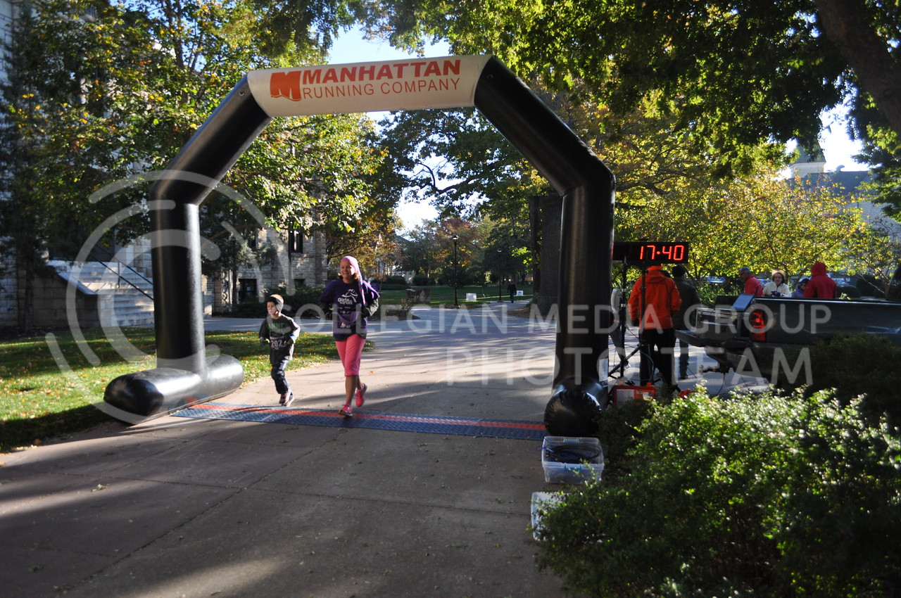 Runners cross the finish line of the C. Clyde Fun Run the morning of Oct. 28, 2017. The 5K fun run and Midge's Mile Fun Walk was held to raise money for Shepherd's Crossing, a community charity that helps residents pay bills and rent when they are in hard times.