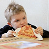 C & M Pizza of Leominster celebrated 55 years in business with a ribbon cutting on Tuesday morning, March 19, 2019. for the entire day they had slices for 55 cents. Trying to enjoy his slice is Dawson Lehtinen, 5, of Lunenburg. SENTINEL & ENTERPRISE/JOHN LOVE