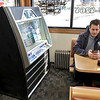 C & M Pizza of Leominster celebrated 55 years in business with a ribbon cutting on Tuesday morning, March 19, 2019. for the entire day they had slices for 55 cents. SAhawn Gerry checks his phone as he waits for the ribbon cutting next to him is jukebox that they have had for ever. SENTINEL & ENTERPRISE/JOHN LOVE