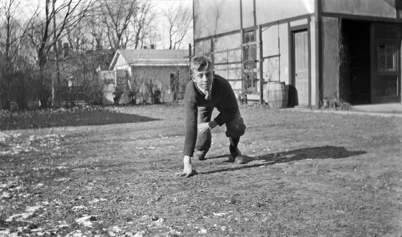 #89 Rowland CRS in football attire in backyard of 109 N Walnut Ave Lansing 1917