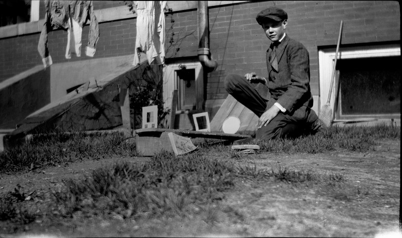 #82 Burr with BoyScout experiment - kneels behind 109 N Walnut St house 1920