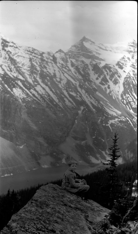 # 184 George on rock with Lake Louise & rockies in background