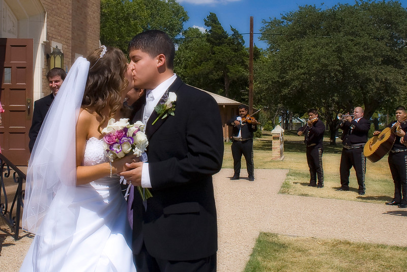 Kiss outside the church while mariachis play in the background