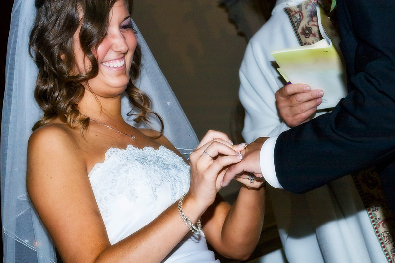 The bride smiles as she puts on the ring on him
