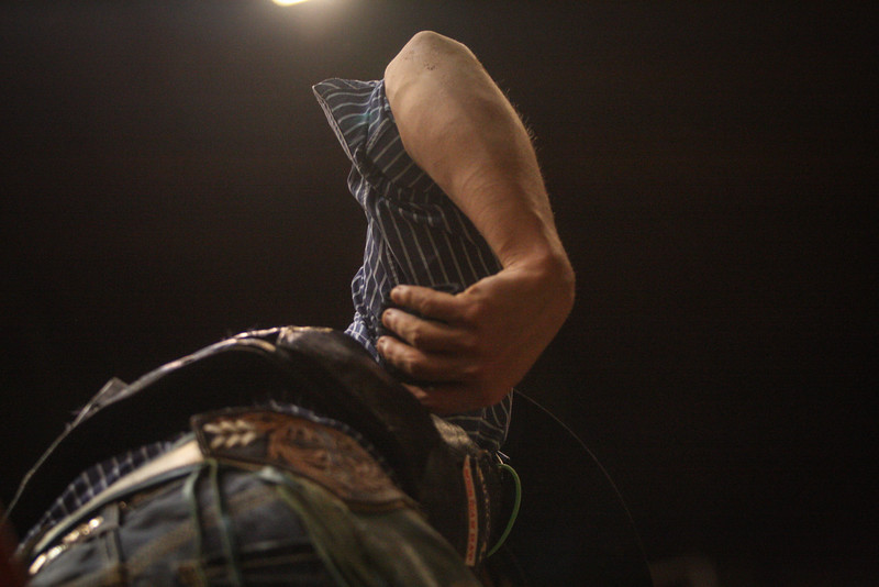 A cowboy reflexively touches a sore spot after being bucked off a bronc at the cowtown rodeo in Ft. Worth, TX,