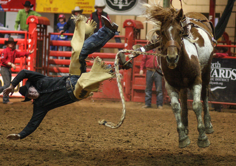 His boot still in the stirrup, a cowboy is caught mid-air at the Ft. Worth cowtown rodeo July 3, 2015.