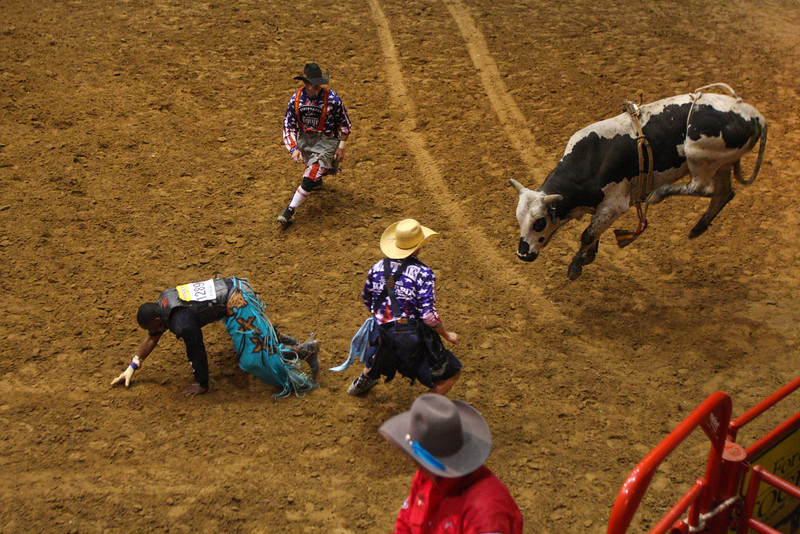 Rodeo clowns distract a bucking bull at the Ft. Worth cowtown rodeo July 3, 2015.