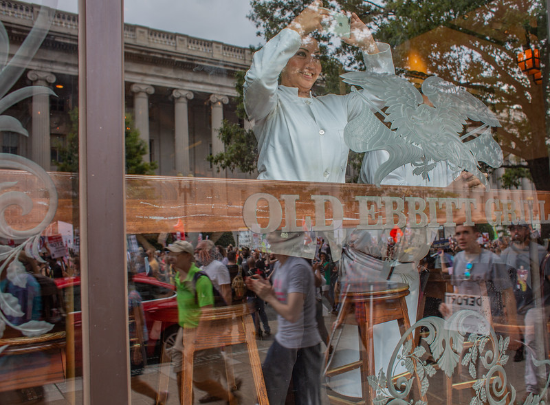Washington, DC - August 12: Waiters at a local restaurant near the White House take pictures of counter protesters to a white nationalist rally, Sunday August 12, 2018.