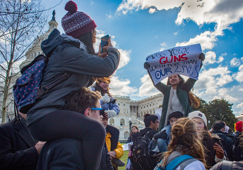 "Washington, D.C. : 3/14/18  <br /> Outside the Capitol, students hold up signs and shout, ""No more guns!"" while senators greet them."