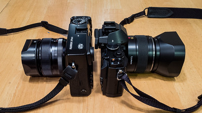 Fuji X-Pro 1 size compared to Olympus OM-D E-M5. Both cameras have a 50mm equiv lens attached. The 35mm f/1.4 for the Fuji and the 25mm f/1.4 for the Olympus