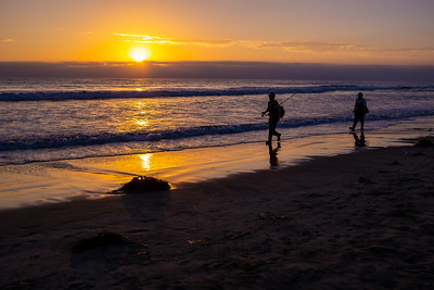Fishermen walk by on a beach in San Diego at sunset