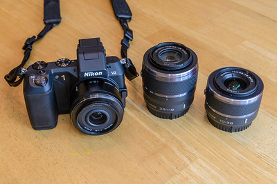 Nikon 1 V2 camera with 18.5mm f/1.8 lens attached.  30-110mm and 10-30mm lenses to the right.