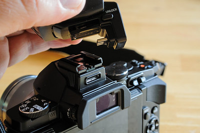 The OM-D has a hot-shoe as well as a little smart connection to the rear and below the shoe.  The included flash uses the smart connection.