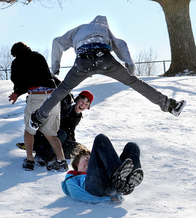 Adam Lund, bottom, slides under a jumping Cian O' Miatiu, while Matt Hise, with cap, laughs in the background. These Fairview High School students were taking a break from finals on Wednesday.<br /> December 14, 2011 / Cliff Grassmick