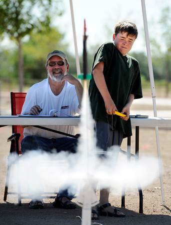 Colin Bruce, 12, launches his rocket during the 4-H Rocket Launch competition, one of the first events of the Boulder County Fair. Judge Warren Musselman is on the left.<br /> Cliff Grassmick / July 27, 2011