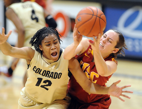 Ashley Wilson, left, of Colorado, and Jacki Gemelos  of Southern California, both reach for a loose ball during the second half of a WNIT game on March 27, 2011 in Boulder.<br /> Cliff Grassmick / March 27, 2011