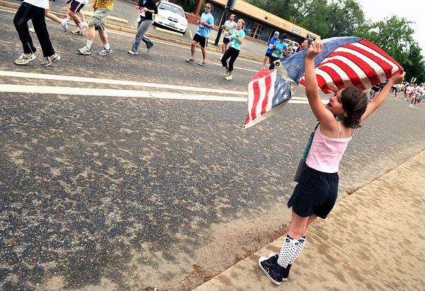"Elise Jongejan, 7, of Denver, shows her american spirit by waving the flag during the Bolder Boulder 10K Race on Monday, May 30, in Boulder. For more photos and video of the Bolder Boulder go to  <a href=""http://www.dailycamera.com"">http://www.dailycamera.com</a><br /> Jeremy Papasso/ Camera"