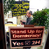 "Eric Medema, of Boulder, carries his protest sign towards the door on Thursday, Oct. 13, during a sign making party at the Rocky Mountain Peace and Justice Center at 3970 Broadway in Boulder. For a video of of the sign making party go to  <a href=""http://www.dailycamera.com"">http://www.dailycamera.com</a><br /> Jeremy Papasso/ Camera"