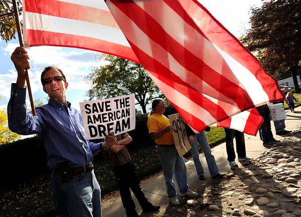 "Joel Koenig, of Boulder, left, holds an american flag along with a protest sign on Friday, Oct. 14, during the ""Occupy Boulder"" rally near the intersection of Canyon Boulevard and 26th Street in Boulder. For more photos of the rally go to  <a href=""http://www.dailycamera.com"">http://www.dailycamera.com</a><br /> Jeremy Papasso/ Camera"