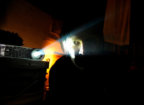"Andrew Novick, of Denver, looks through the light of a projector while setting up for a slideshow on Friday, Dec. 9, during a benefit concert at the Rhinoceropolis warehouse on Brighton Boulevard in Denver. Novick is well-known for his large collection of random objects including images used for slideshows. For more photos and video of the concert go to  <a href=""http://www.dailycamera.com"">http://www.dailycamera.com</a><br /> Jeremy Papasso/ Camera"